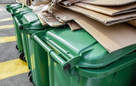 Paper and cardboard on green recycle bins