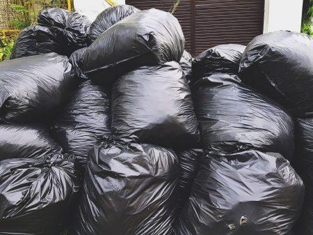 Pile of Black Plastic Garbage Bags on Street